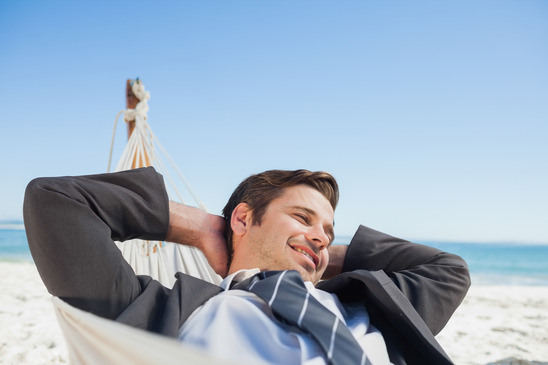 Businessman relaxing in hammock at beach on sunny day